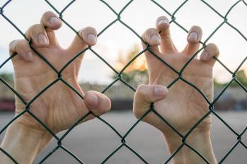 manos-del-inmigrante-detrc3a1s-de-la-frontera-o-de-la-cerca-en-la-puesta-del-sol-97920954